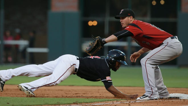 El Paso's Manuel Margot dives back to first base as Sacramento first baseman Grant Green waits for the pickoff throw Thursday. The ball bounced past Green, allowing Nick Noonan to score and Margot to reach second.