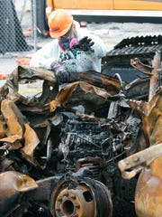 A crew member removes residue from the engine of a burned truck during the demolition of the damaged Irondequoit DPW at the Irondequoit Town Hall campus.