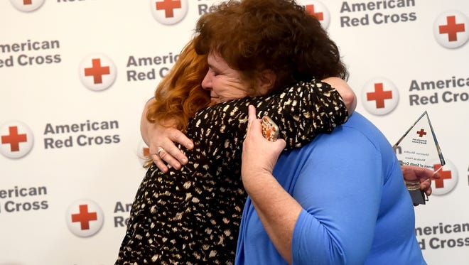 """Jane Hershey, right, embraces Shannon Shutika after Shutika and three of her co-workers from SpiriTrust Lutheran, recieved the """"Medical"""" award at the American Red Cross """"Spirit of the Hero"""" breakfast.  Shutika and the other recipients saved the life of Hershey's mother, Iona Klepper, in the Hanover facility in November of 2015."""