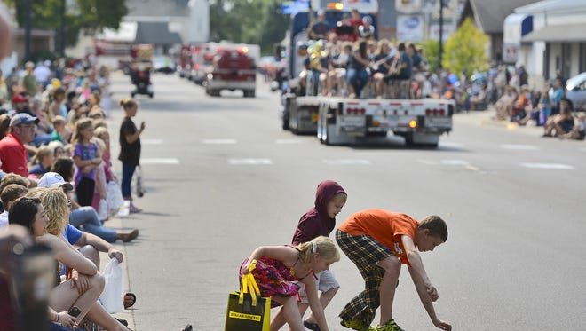 Children dart out after a harvest of candy during the 2015 Pierz Oktoberfest parade.