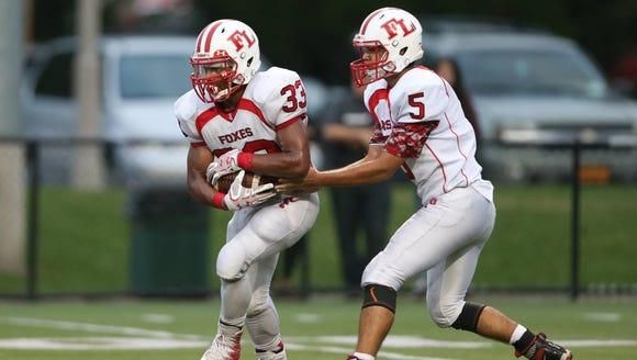 Fox Lane quarterback Matt Bodine, 5, hands off to running