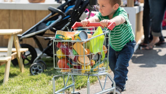 Will Dimick, 2, pushes a shopping cart full of plastic groceries Thursday, June 7, 2018, at the new Sprout City playground in Port Huron.