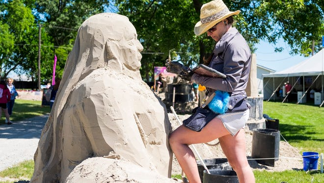Melineige Beauregard works on her sculpture of a goddess of life and time during the first day of Blue Water Sandfest Friday, July 6, 2018, at the Fort Gratiot Lighthouse.