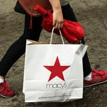 A woman carries a Macy's shopping bag in New York City.
