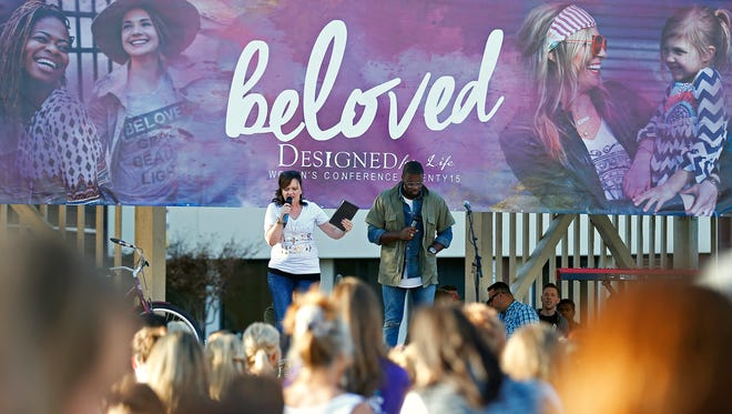 James River Church pastor Debbie Lindell and Texas-based pastor Robert Madu pray with the attendees of the Sisterhood in the City event held at Park Central Square in downtown Springfield, Mo. on Oct. 10, 2015 as part of the Designed Sisterhood conference held by James River Church.