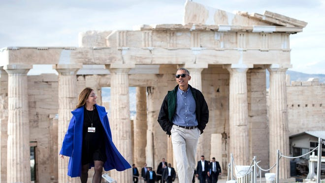 President Obama walks from the Propylaia with Eleni Banou, Ministry of Culture director of Ephorate of Antiquities for Athens, during a tour of the Acropolis on Wednesday in Athens. Obama will sketch out his vision of democracy at a time of mounting global populism, seeking to soothe European allies anxious over a Donald Trump presidency.