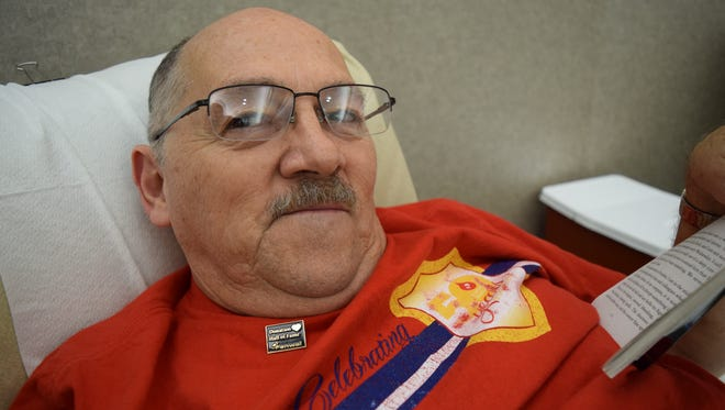 Wendell Clark reads while donating blood.