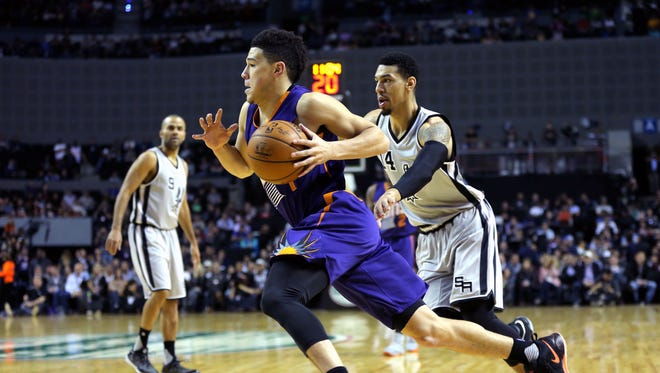 Phoenix Suns guard Devin Booker (1) drives against San Antonio Spurs guard Danny Green (14) in the first half during the NBA game at the Mexico City Arena.