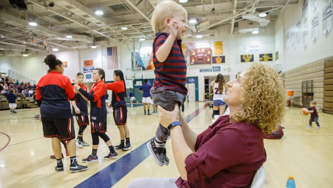 Electra Viveros holds her son Asher in the air before the start of a basketball game at La Quinta High School, Feb. 10, 2017.