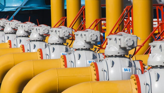 Pipes and valves with handles are on the gas compressor station.