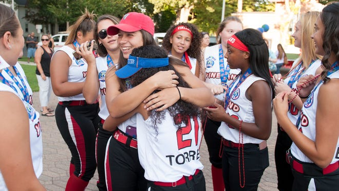 Members of the Vineland Pigtail 14U All-Stars, center l-r, Nicole Ortega and Ariana Torres hug as they are surrounded by teammates prior to being honored for their World Series win, at a ceremony at Vineland City Hall on Friday.  08.04.17
