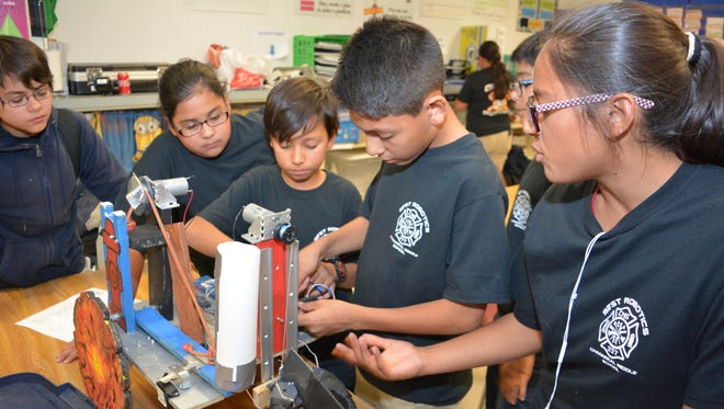 Isaac Garcia and Kevin Ramos, center, tinker with the robotic arm creation that helped the team win first place overall in the BEST competition held in October at New Mexico State University