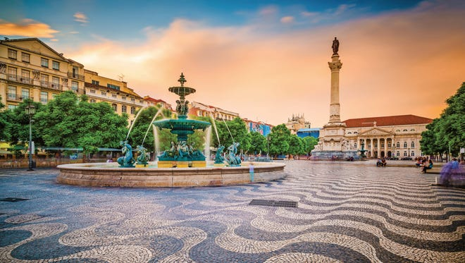 Drink in the atmosphere at Rossio Square, a lively area in Lisbon where people stop to sit and relax.