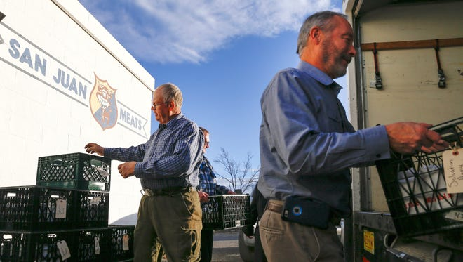 Tommy Bolack, left, Doyle Hodges and Eric Schoen load a truck with donated meat on Wednesday at San Juan Meats in Kirtland.