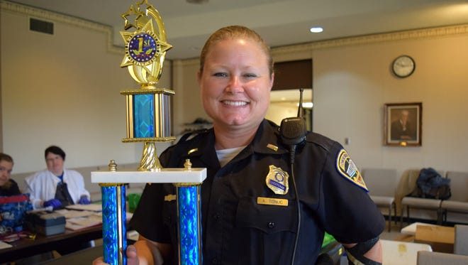 Richmond Police Department Lt. Aly Tonuc holds the Cuffs and Ladders Blood Drive trophy after RPD topped the Richmond Fire Department in Friday's friendly competition.