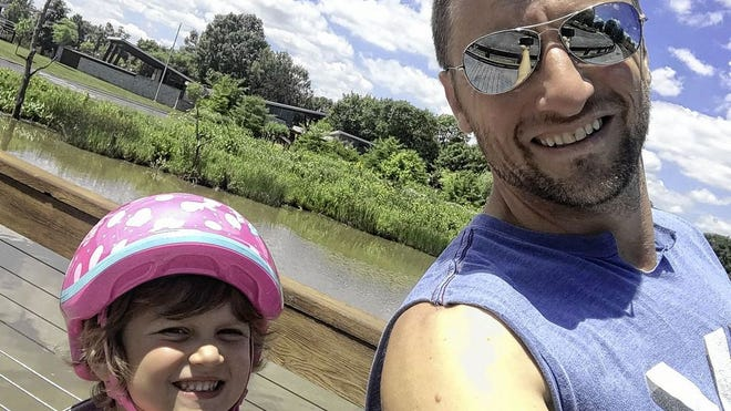 Brian Stevens and his 4-year-old daughter, Quinn, take time out from cycling for a photograph. Stevens, 41, said he and his wife, Allison, learned their daughter, Quinn, would require treatment for stage 4 cancer in early 2019 at age 2.
