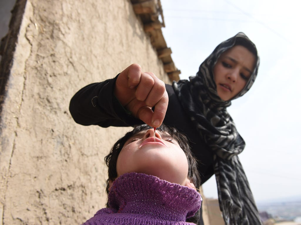 A health worker administers a polio vaccine to a child on March 16 in Kabul, Afghanistan.