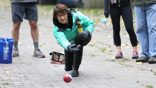 Kathleen Graham throws her ball during a game of back ally bocce just west of 42nd Street and College Avenue.