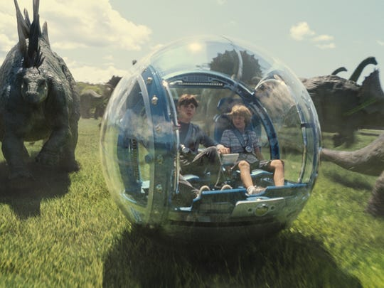 Zach (Nick Robinson) and Gray (Ty Simpkins) roll through the Jurassic World landscape with stampeding Stegosaurs and Triceratops.