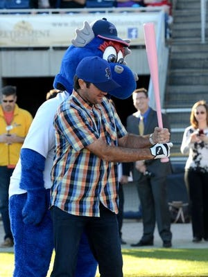 Kazoo, the Blue Wahoos mascot, gives golfer Bubba Watson some batting tips on Monday after it was announced that Watson would become part owner of the Wahoos.