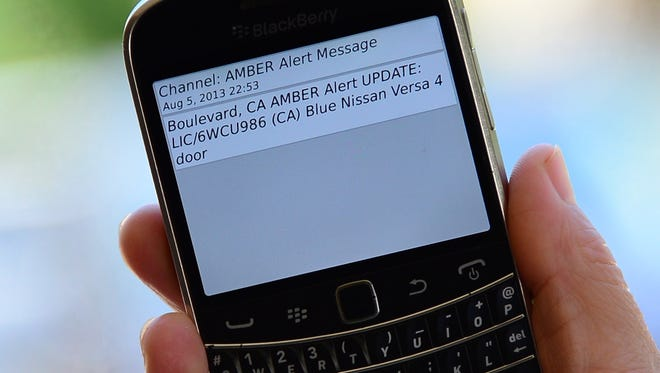 A cellphone displays the AMBER Alert issued late on Aug. 5, 2013, in Los Angeles, in reference to murder and kidnapping suspect James Lee DiMaggio, marking the first time officials notified the public of a statewide AMBER Alert via cellphone.