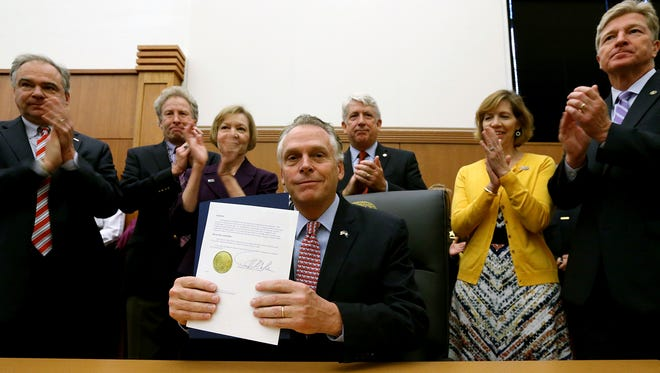 Virginia Governor Terry McAuliffe, center, smiles after signing an executive action to prevent gun violence as from left to right, U.S. Sen. Tim Kaine, D-VA, Andy Parker, his wife Barbara Parker, parents of slain WDBJ-TV reporter Alison Parker, Virginia Attorney General Mark Herring, Lori Haas, whose daughter Emily was injured in the VA Tech shootings, and Virginia Secretary of Public Safety and Homeland Security Brian Moran applaud during a press conference in Richmond, Va., Thursday, Oct. 15, 2015.  (Bob Brown /Richmond Times-Dispatch via AP) MANDATORY CREDIT