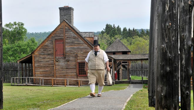 Karl Koster, in the interpretive role of a gentleman, heads from the great hall toward the canoe warehouse June 17, 2016, at Grand Portage National Monument. The site is one of a handful of National Park Service sites in Minnesota. The NPS is marking its 100th anniversary. The monument will mark its fur-trading history with a rendezvous that will bring a tall ship to the bay Aug. 13. When actual traders and voyageurs congregated at the site, they would have numbered 2,000.