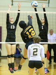 Up in unison to block against Lansing Christian's Isabelle