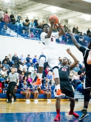 William Penn's Kristopher Johnson (5) rises for a layup