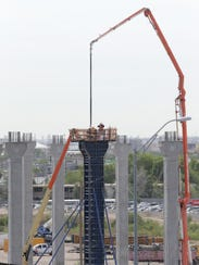 Workers fill a pillar with concrete as they work to