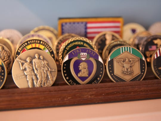 Medals, including a Purple Heart, sit atop a mantle