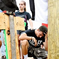 Cody Stern, a 2014 Red Lion High School graduate, front, is comforted by the hand of Red Lion student Lindsay Wilhelm, back, at a memorial built at the base of a utility pole on Slab Road in Lower Chanceford Township for their friends and classmates Stone Hill and Nicholas Mankin, the day after the two Red Lion students died in a fiery crash.