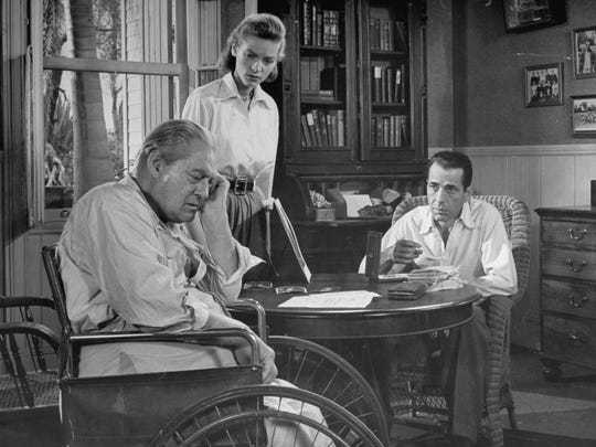 "Married actors Humphrey Bogart, right,  and Lauren Bacall with actor Lionel Barrymore (in wheelchair) in scene from the 1948 film ""Key Largo."""