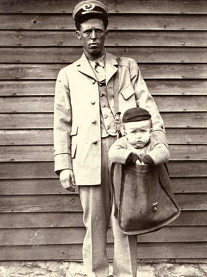 This city letter carrier posed for a humorous photograph with a young boy in his mailbag.