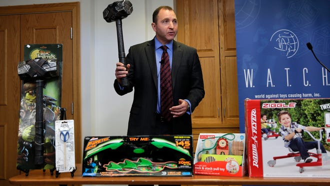 James Swartz, director of World Against Toys Causing Harm Inc., holds up toy battle hammer at Children's Franciscan Hospital in Boston.  The consumer watchdog group has released its annual list of what it considers to be the 10 most unsafe toys.