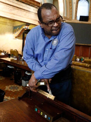 Joe Robinson, a Mississippi House of Representatives porter, removes the name plate of long-time Democratic lawmaker Bennett Malone, of Carthage, who decided not to run for reelection, in chambers at the Capitol in Jackson. Robinson is removing 26 nameplates from the desks in the chamber, each one representing a new House member, as the staff readies for the opening of the 2016 session.