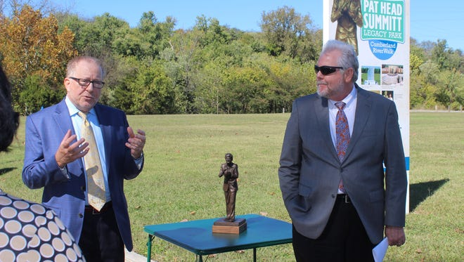 Frank Lott, left, and Richard Stevens, both on the Pat Head Summitt Legacy Park committee, unveil design and artwork for the future site Tuesday along the Cumberland RiverWalk.