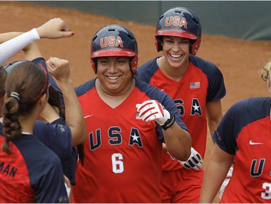 Crystl Bustos, center, celebrates after hitting a homer