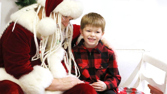Conner VanDeHey, 5, of Salem, tells Santa Claus what he wants for Christmas during Magic at the Mill Saturday, Dec. 19, 2015, in Salem, Ore.