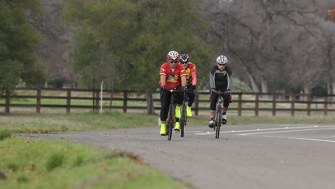 Casey Kerrigan, from left, Scott Kirkland and Dan Martin ride their bikes Tuesday as rain begins to fall at Shasta View Drive near Lema Ranch in Redding.