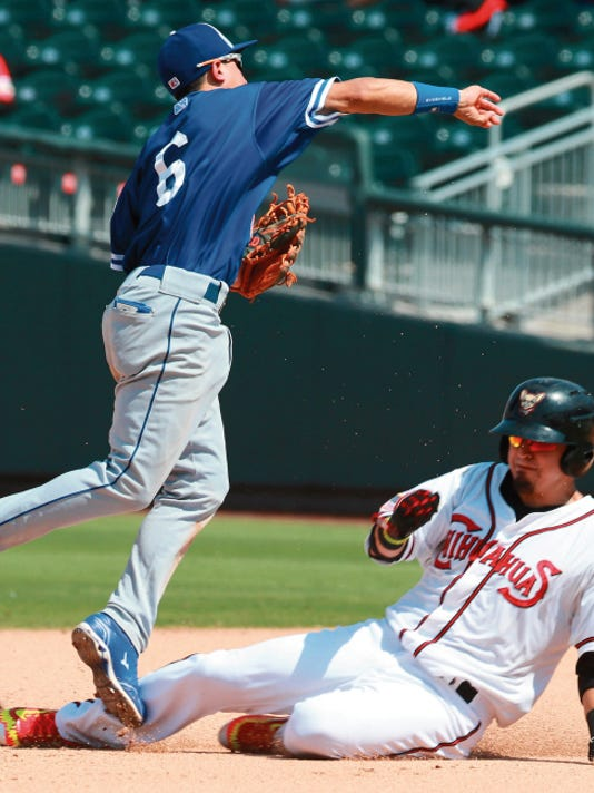 El Paso's Ramiro Pena slides beneath Oklahoma City shortstop Ronny Torreyes who was throwing to first to complete a double play Sunday.