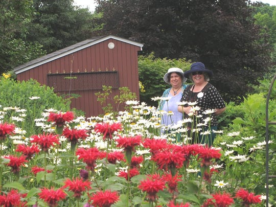 Donna Beech, left and Carla Van Hoy, both of Waterbury Center, pause while viewing a garden in Hinesburg. The women were among 400 people to sign up for the Flynn Garden Tour this year.