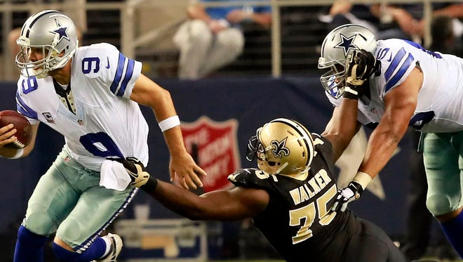 New Orleans Saints defensive end Tyrunn Walker looks to sack Dallas Cowboys quarterback Tony Romo on Sept. 28, 2014. Walker has signed with the Detroit Lions.