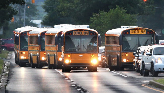 School buses taking Indianapolis students back to school at North Central High School in Washington Township for the first day of classes get ready to turn into the school off of  East 86th Street on Monday, August 3, 2015.