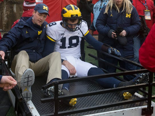 Michigan quarterback Brandon Peters is carted from