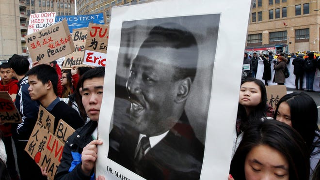 Students with the Asian Americans United group hold a photograph of Rev. Martin Luther King Jr. as they join a large crowd in a march to honor King, Monday, Jan. 19, 2015, in Philadelphia. (AP Photo/Mel Evans)