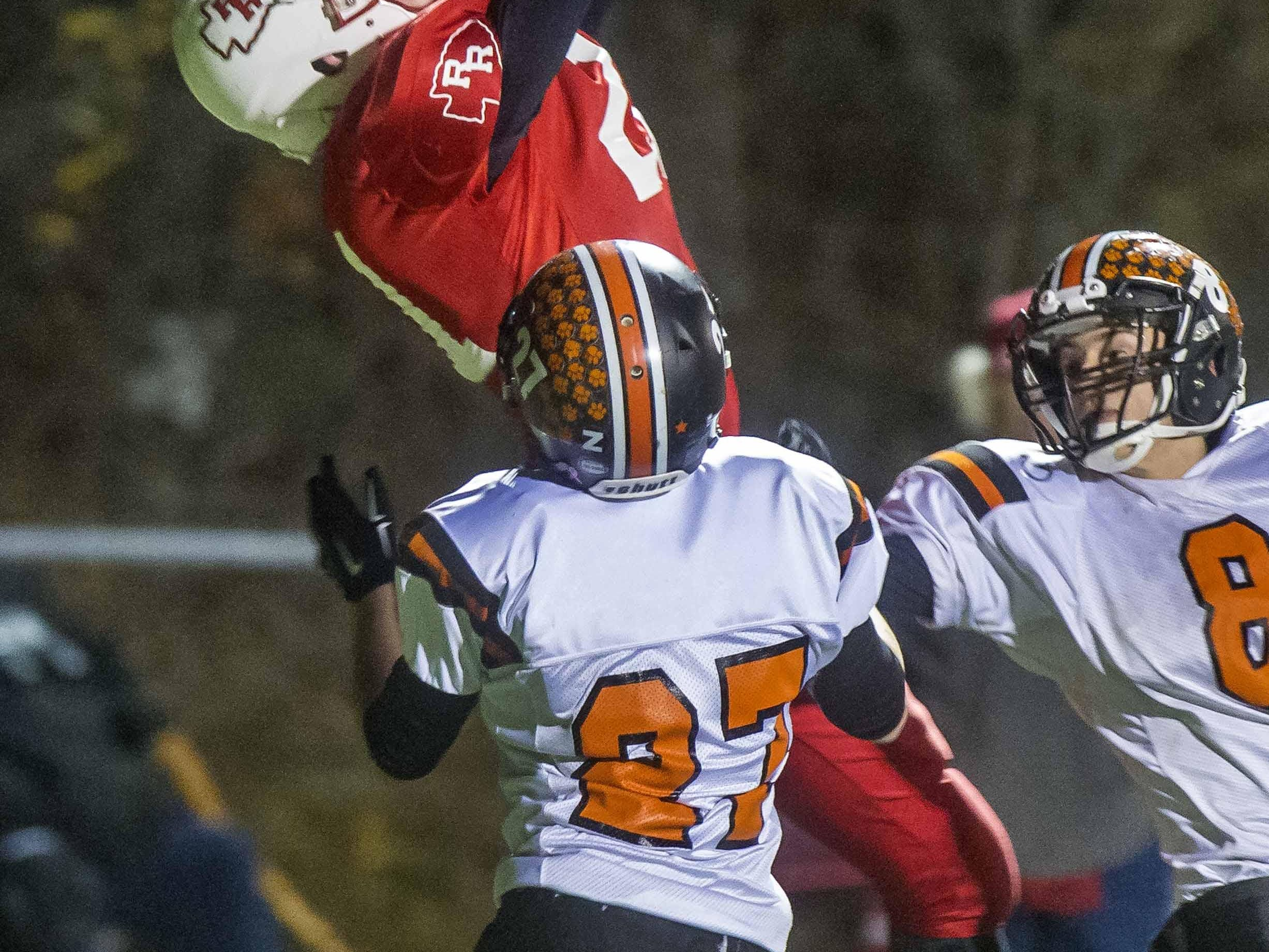 Rutland's Cam Slade, center, caches a touchdown pass over Middlebury's Jack Hounchell , left, and Chase Messner in the D1 state football championship in Rutland on Saturday, November 7, 2015.