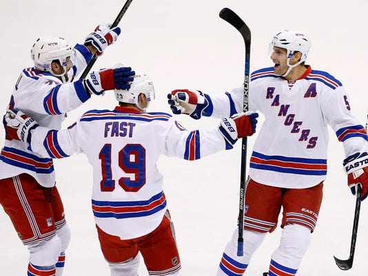 New York Rangers' Jesper Fast (19), of Sweden, celebrates his goal against the Arizona Coyotes with Dan Girardi (5) and Jarret Stoll, left, during the first period of an NHL hockey game Saturday, Nov. 7, 2015, in Glendale, Ariz. (AP Photo/Ross D. Franklin)