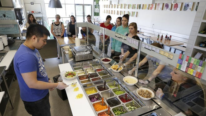 Trevor Vesleno, left, a corporate trainer with Freshii, explains how to prepare a dish to new employees during June training at the new Freshii restaurant in Buchanan.