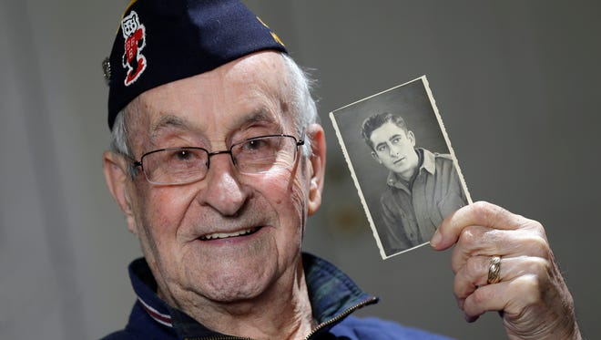 Ralph Ticcioni of New Berlin holds a photo of himself taken in 1944 in Belgium while serving with the 573rd Signal Air Warning Battalion assigned to the 82nd Airborne.